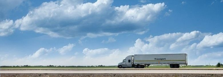 Semi Truck Driving With Clouds In The Background.